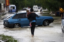 A local resident walks with her child through a flooded street in the southern Russian town ofKrymsk