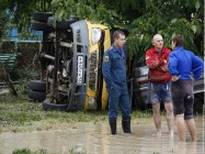An emergency service worker stands near an overturned car in the southern Russian town ofKrymsk