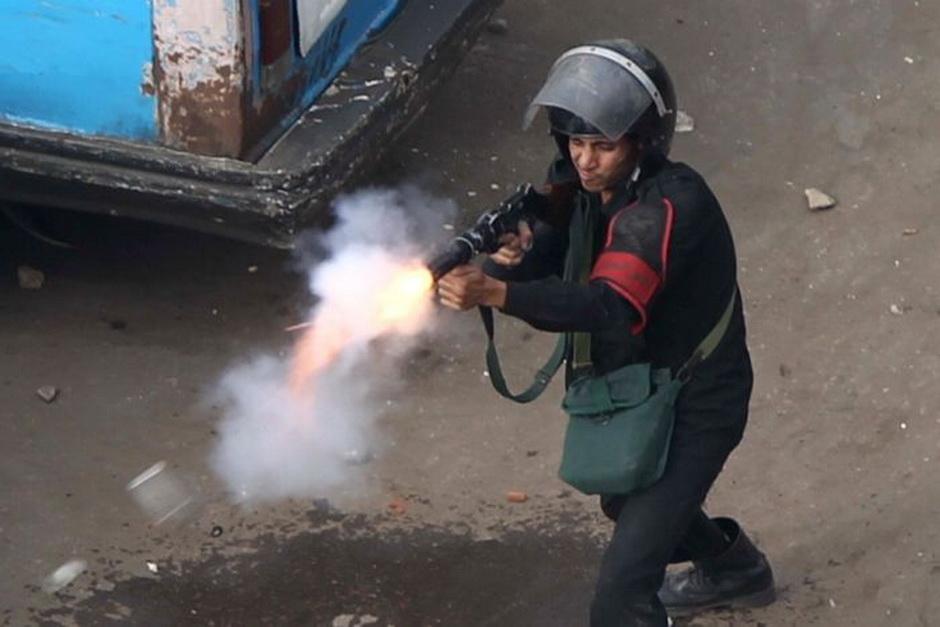 An Egyptian police officer fire tear gas