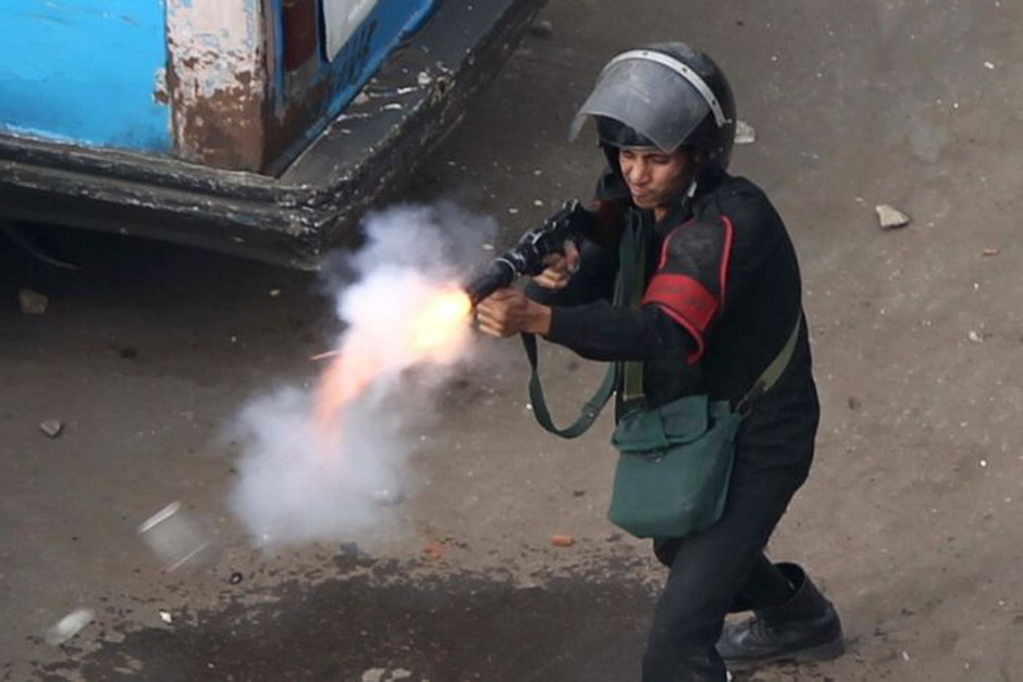An Egyptian police officer fire tear gas