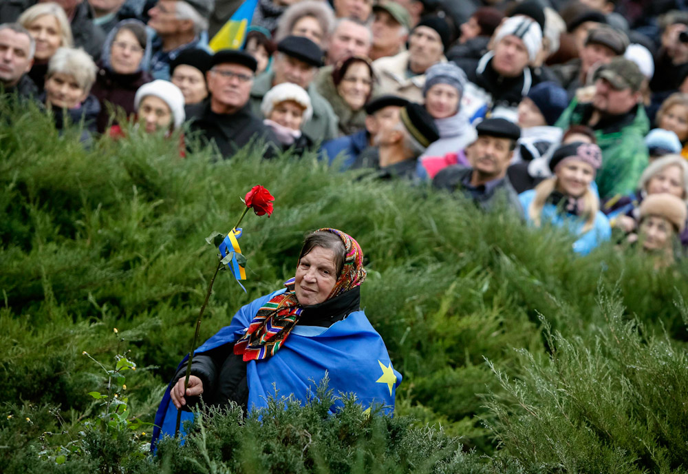 A protester holds a flower as she joins other demonstrators during a rally to support EU integration in central Kiev