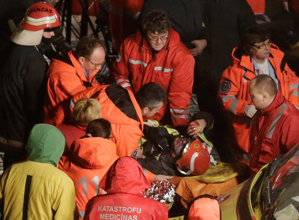 Paramedics inspect a firefighter on a stretcher after he was moved from the collapsed Maxima supermarket in Riga