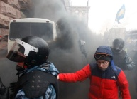Ukrainian riot police leave a bus after protesters threw a smoke bomb, outside City Hall inKiev
