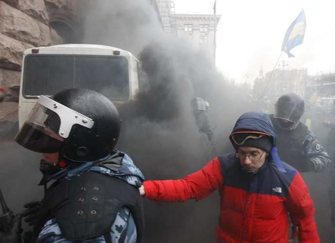 Ukrainian riot police leave a bus after protesters threw a smoke bomb, outside City Hall in Kiev