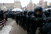 A line of Ukranian riot police moves past pro-European integration protestors in Independence Square inKiev