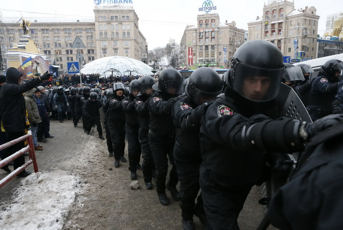 A line of Ukranian riot police moves past pro-European integration protestors in Independence Square in Kiev