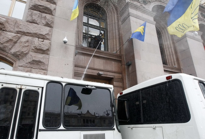 A pro-European integration protester sprays water at police buses in Kiev