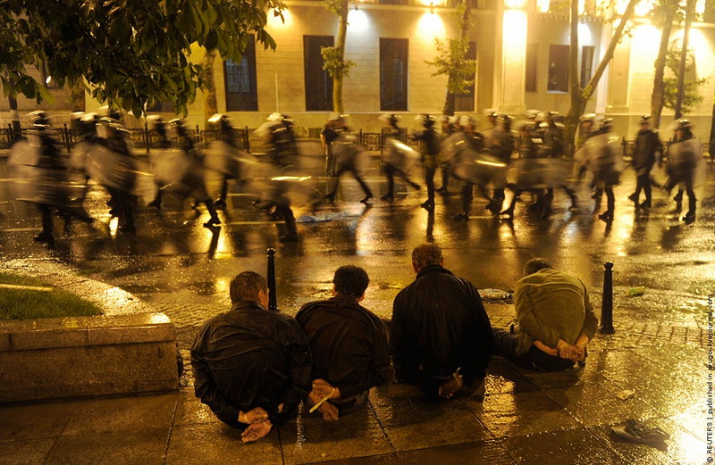 Detained protesters sit on the street as riot police leave after clashes in Tbilisi