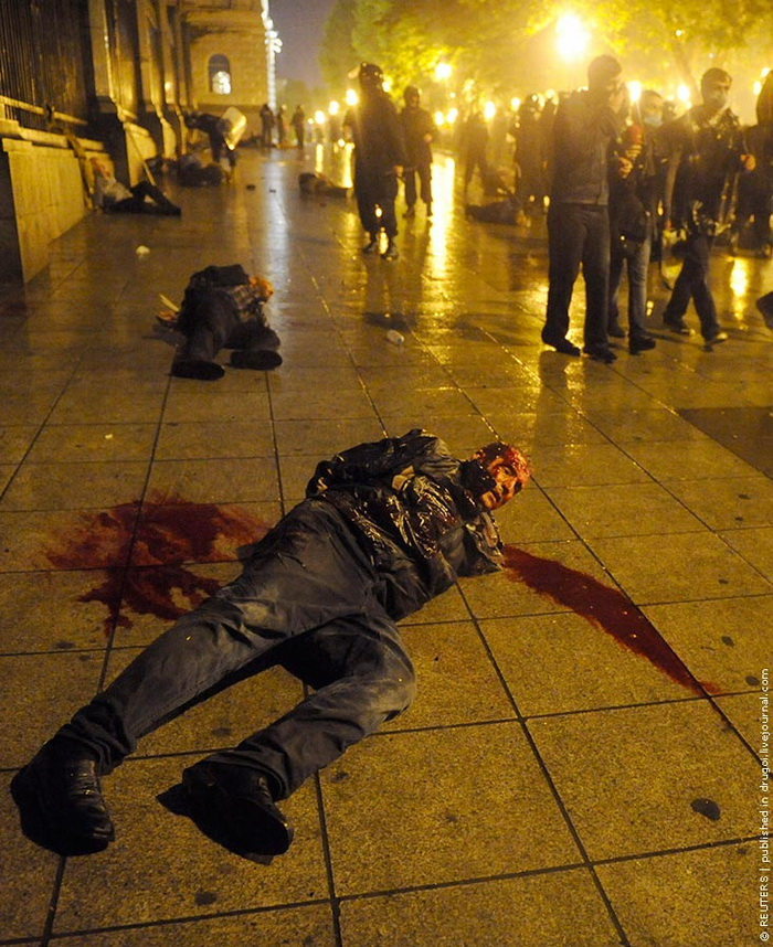 An injured protester lies on the ground after being detained during clashes with police in Tbilisi