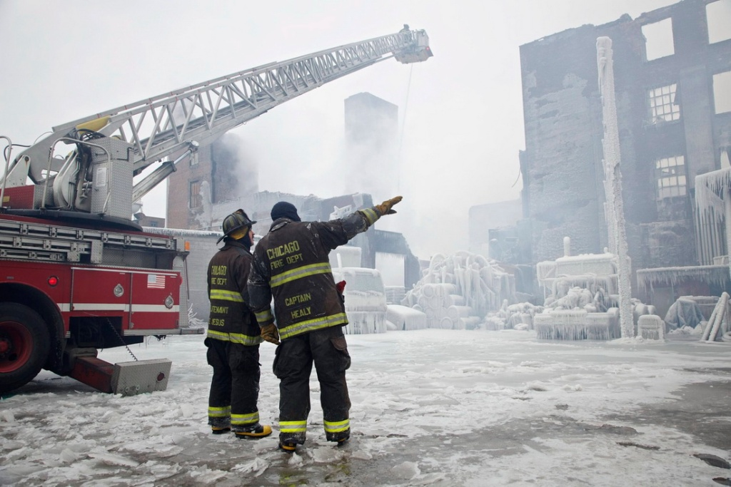 Firefighters spray hotspots on an ice-covered warehouse that caught fire Tuesday night, in Chicago