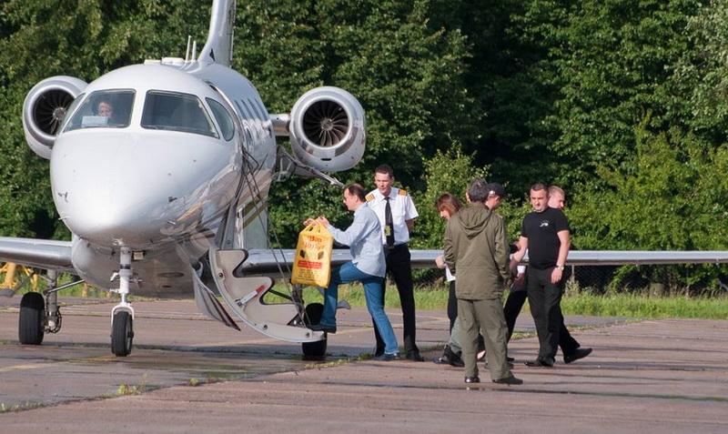 Ляшко карабкается по трапу в самолетик. Не пропустив женщину