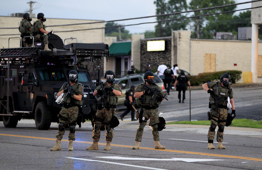 Police wearing riot gear try to disperse a crowd Monday, Aug. 11, 2014, in Ferguson, Mo. The FBI opened an investigation Monday into the death of 18-year-old Michael Brown, who police said was shot multiple times Saturday after being confronted by an officer in Ferguson. Authorities in Ferguson used tear gas and rubber bullets to try to disperse a large crowd Monday night that had gathered at the site of a burned-out convenience store damaged a night earlier, when many businesses in the area were looted. (AP Photo/Jeff Roberson)