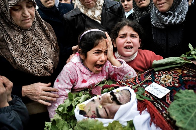 SYRIA - Al Qsair. A child mourns the death of her father who was kidnapped by Shabiha (militias of the regime). The child's father was tortured to death and then his body was left in a main street of Al Qsair, on February 14, 2012.