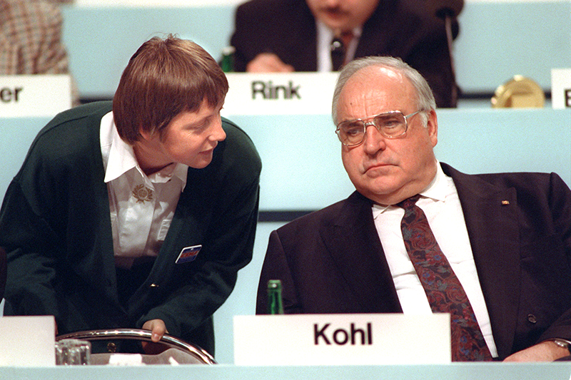 Federal minister for women Angela Merkel talks to her mentor, chancellor Helmut Kohl, at the CDU party conference on the 16th of December in 1991.