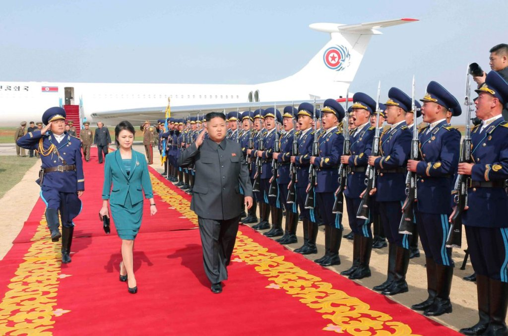 North Korean leader Kim Jong Un (3rd L) salutes as he and his wife Ri Sol Ju walk past the guard of honour upon arriving for the 2014 Combat Flight Contest among commanding officers of the Korean People's Air Force in this undated photo released by North Korea's Korean Central News Agency (KCNA) in Pyongyang May 10, 2014. REUTERS/KCNA (NORTH KOREA - Tags: POLITICS MILITARY TRANSPORT) ATTENTION EDITORS - THIS PICTURE WAS PROVIDED BY A THIRD PARTY. REUTERS IS UNABLE TO INDEPENDENTLY VERIFY THE AUTHENTICITY, CONTENT, LOCATION OR DATE OF THIS IMAGE. FOR EDITORIAL USE ONLY. NOT FOR SALE FOR MARKETING OR ADVERTISING CAMPAIGNS. THIS PICTURE IS DISTRIBUTED EXACTLY AS RECEIVED BY REUTERS, AS A SERVICE TO CLIENTS. NO THIRD PARTY SALES. NOT FOR USE BY REUTERS THIRD PARTY DISTRIBUTORS. SOUTH KOREA OUT. NO COMMERCIAL OR EDITORIAL SALES IN SOUTH KOREA