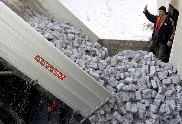 Tons of shredded and compressed banknotes are unloaded from a truck at the Foundation to Help Autism in Miskolc